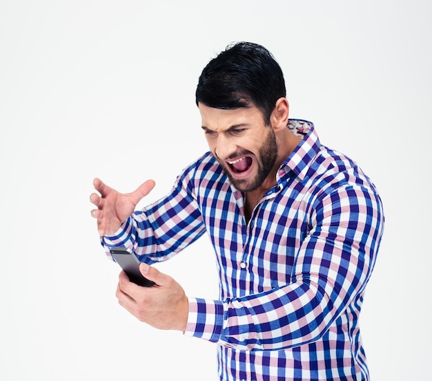 Portrait of angry man shouting on smartphone isolated on a white wall