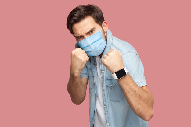 Portrait of angry man with surgical medical mask in blue casual style shirt standing with boxing fists and looking at camera and ready to attack. indoor studio shot, isolated on pink background.