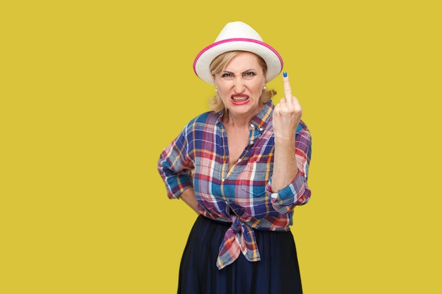 Portrait of angry modern stylish mature woman in casual style with hat and eyeglasses standing with middle finger fuck sign and looking at camera. indoor studio shot isolated on yellow background.