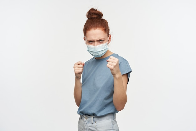 Portrait of angry redhead girl with hair gathered in a bun. wearing blue t-shirt and protective face mask. clench her fists, ready to fight.  isolated over white wall
