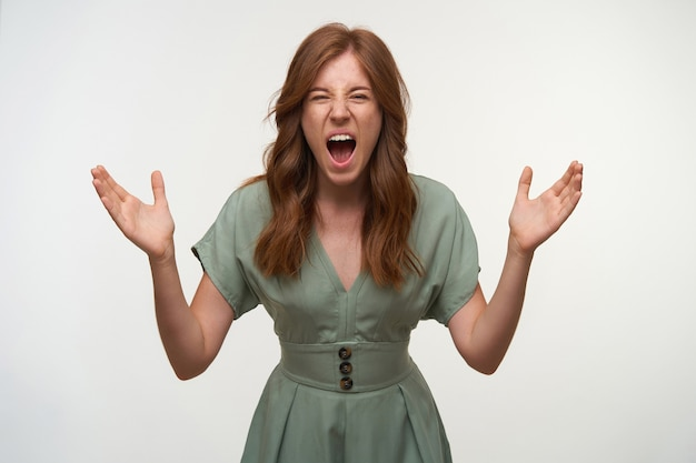 Portrait of angry redhead woman with raised palms wearing vintage dress in pastel color, screaming violently and looking, isolated