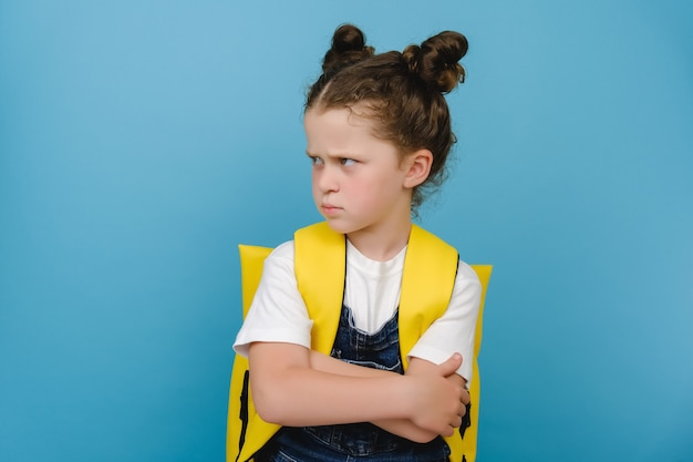 Portrait of angry sad little schoolgirl, crossed arms looking to side, does not want to go to school, wears yellow backpack, posing isolated over blue studio background. children's emotions concept