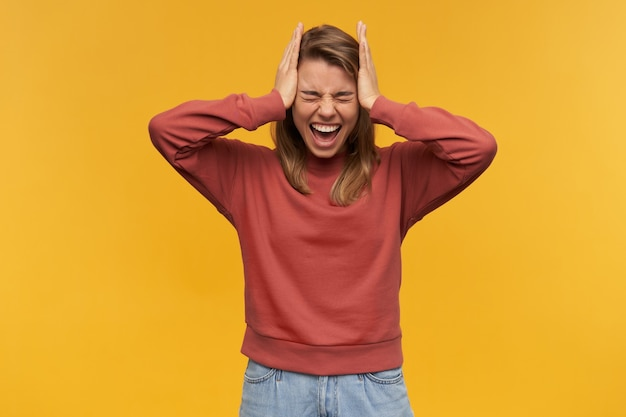 Ritratto di giovane donna urlante arrabbiata in felpa di terracotta con gli occhi chiusi e le mani sulla testa urlando e avendo un mal di testa isolato sopra il muro giallo