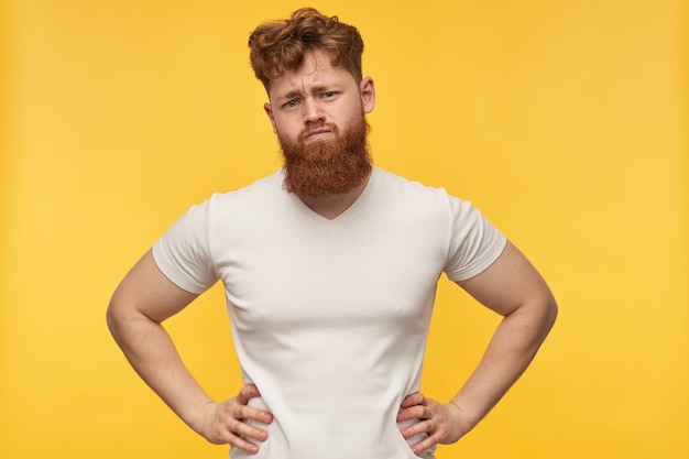 Portrait of angry and serious young bearded guy, wears blank t-shirt, raised his hands and eyebrows on yellow.