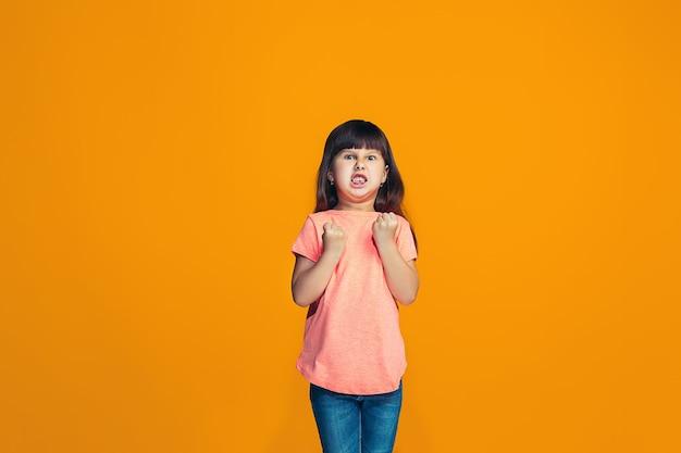 Portrait of angry teen girl on a orange studio background