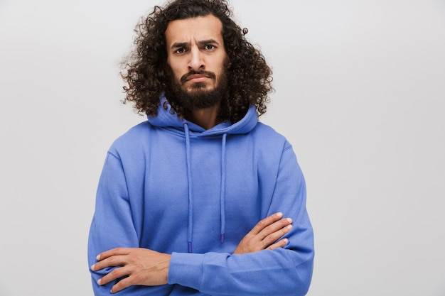 Portrait of angry unshaven man in casual sweatshirt standing with arms crossed isolated on white