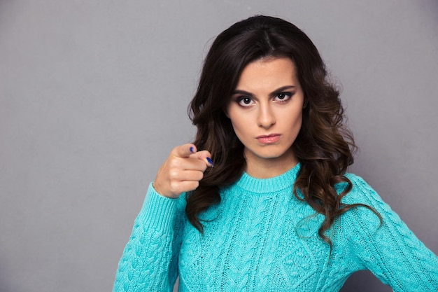 Portrait of angry woman pointing finger over gray wall