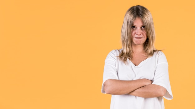 Portrait of angry woman standing on yellow background