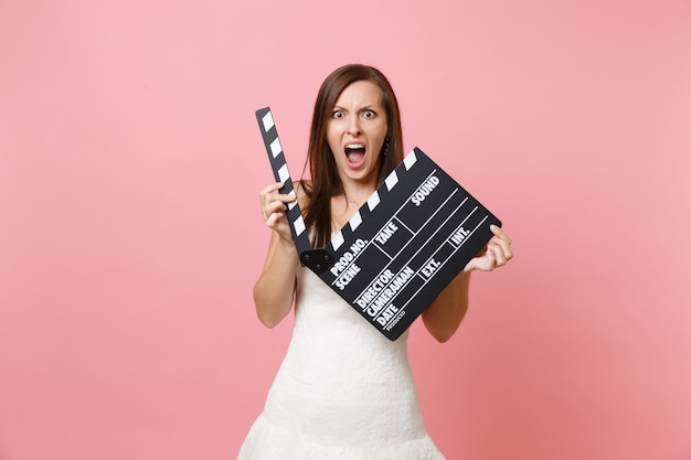 Portrait of angry woman in white dress screaming holding classic black film making clapperboard