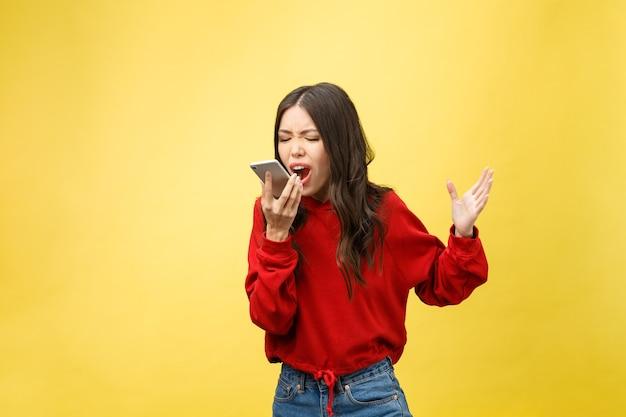 세로 화가 젊은 아시아 여자는 서있는 동안 휴대 전화에 실망