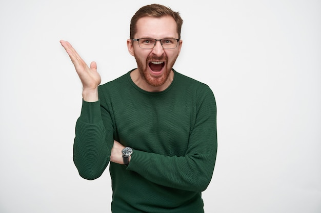 Portrait of angry young bearded guy in eyewear with brown short hair raising affectively his hand and screaming fiercely with wide mouth opened, isolated