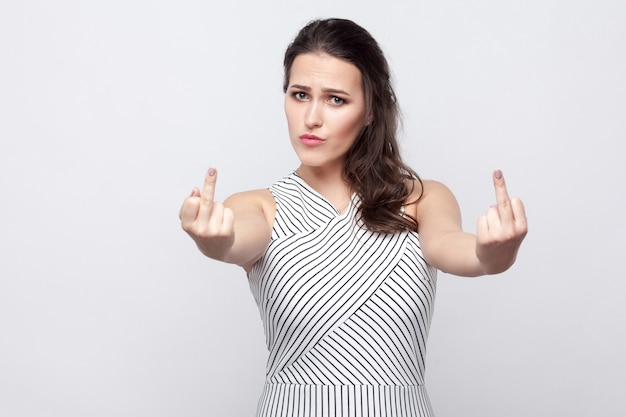 Portrait of angry young brunette woman with makeup and striped dress standing serious face and looking at camera and showing middle finger fuck sign. indoor studio shot, isolated on grey background.