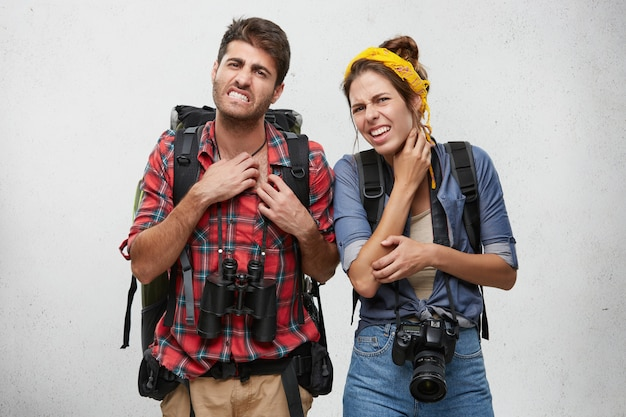 Portrait of angry young couple scratching, feeling annoyed while being bitten by exotic insects or mosquitos, looking at camera with painful expression on their faces. tourism, travel and adventure