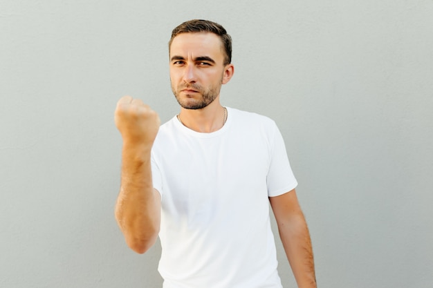 Portrait of an angry young man threatening with a fist isolated over white wall