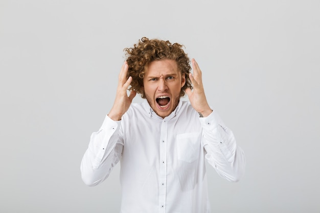 Portrait of an angry young man with curly hair