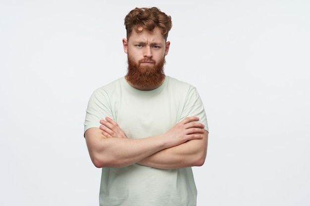 Portrait of angry young redhead with a big beard male, crossed his hands on chest