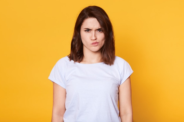 Portrait of angry young woman, frowning over yellow