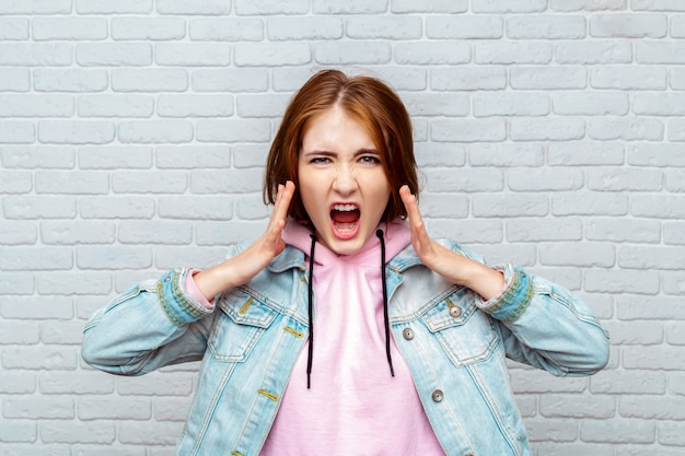 Portrait angry young woman screaming