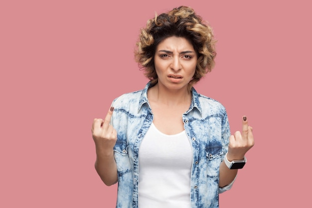 Portrait of angry young woman with curly hairstyle in casual blue shirt standing with middle finger fuck sign and looking at camera with dissatisfied face. studio shot, isolated on pink background.