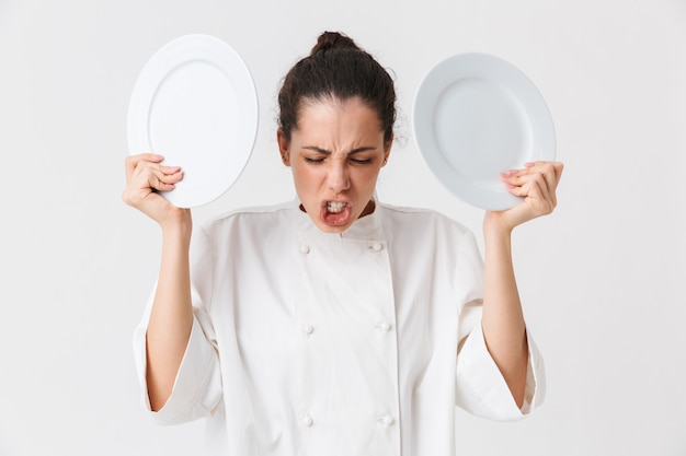 Portrait of an angry young woman with dishes