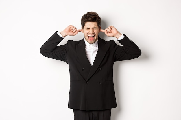 Portrait of annoyed and bothered businessman in black suit, shut ears and yelling, complaining loud noise, standing against white background.