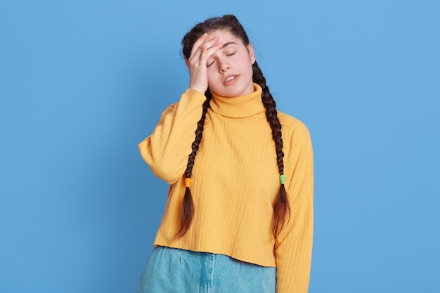 Portrait of annoyed cute female dresses yellow sweater making facepalm gesture, keeps eyes closed, touching forehead in despair and irritation, being upset over blue wall