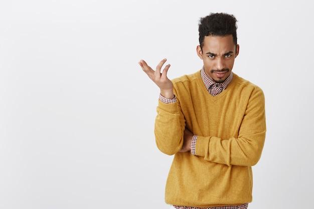 Ritratto di uomo infastidito di bell'aspetto con taglio di capelli afro in abiti gialli, gesticolando, esprimendo confusione, accigliato, essendo scontento e interrogato mentre ascolta l'accusa