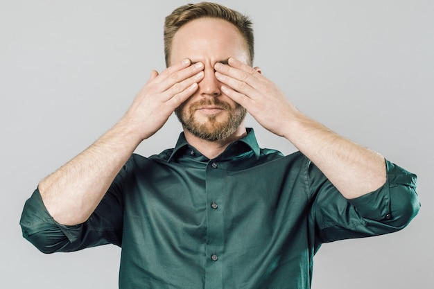 Portrait of annoyed young man covering eyes with hands
