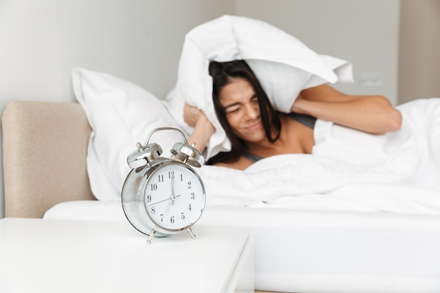 Portrait of annoyed young woman covering ears with pillow due to focused ringing alarm clock in morning, while lying in bed