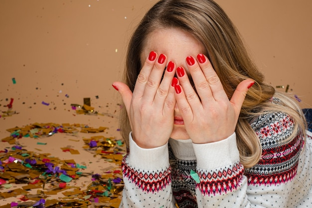 Portrait of anonymous fair-haired caucasian woman with red nails wearing sweater with winter pattern hiding her eyes while laying on the floor with colorful confetti