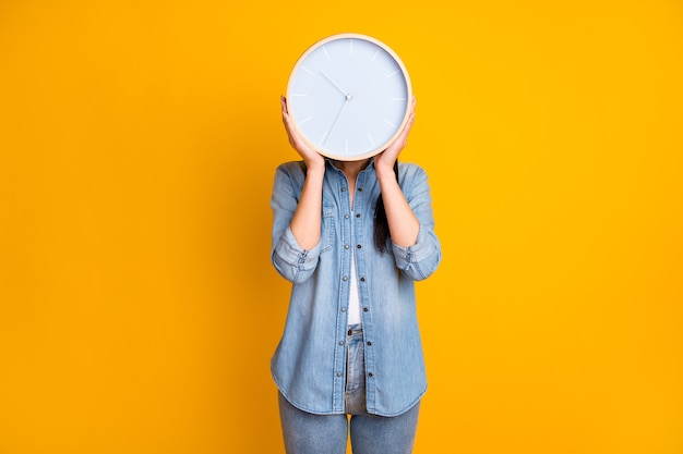 Portrait of anonymous girl hiding behind round face clock