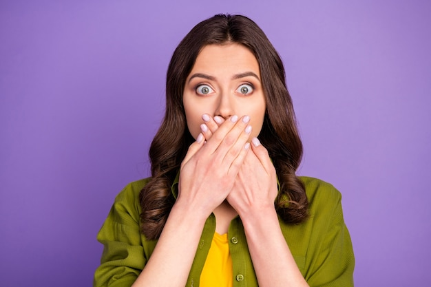 Portrait of anxious amazed girl suddenly tell best friends private secret close cover hands mouth lips wear good look clothes isolated over violet color background