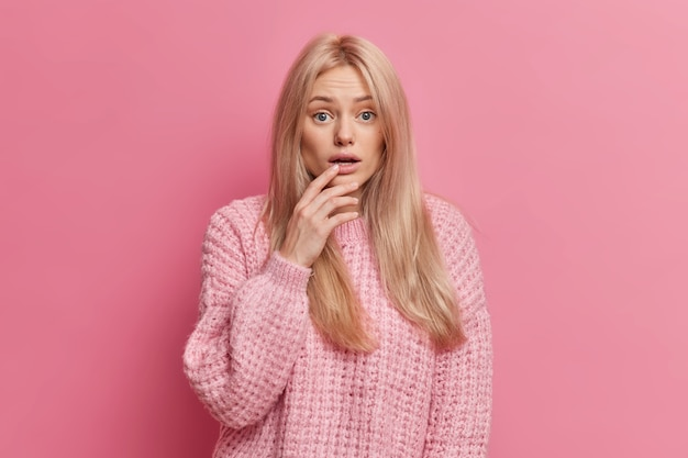 Portrait of anxious blonde woman looks disturbed and concerned, keeps mouth opened stands horrified dressed in casual knitted sweater Free Photo