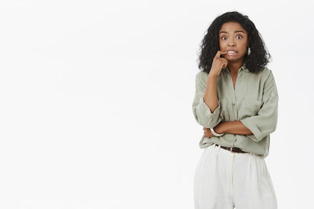 Ritratto di donna dalla carnagione scura carina e femminile ansiosa con acconciatura riccia che stringe i denti dai nervi che mordono il dito