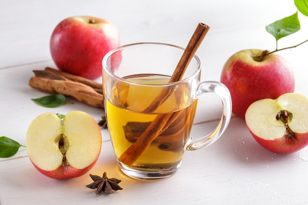 Portrait of apple cider with cinnamon stick on white wooden table