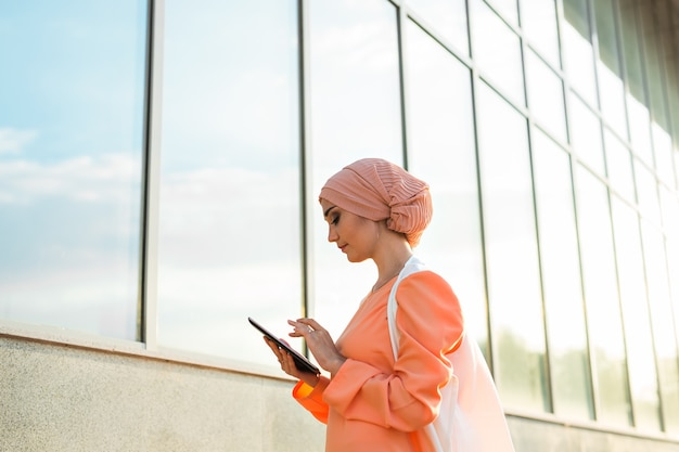 Portrait of an arab businesswoman in hijab holding a tablet.