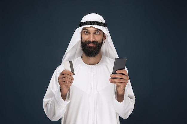 Portrait of arabian saudi businessman on dark blue studio background. man using smartphone for paying bill, online shopping or betting. concept of business, finance, facial expression, human emotions.