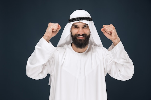 Portrait of arabian saudi businessman on dark blue studio background. young male model standing, smiling and celebrating. concept of business, finance, facial expression, human emotions.