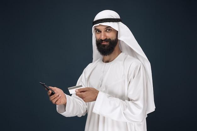 Portrait of arabian saudi businessman on dark blue