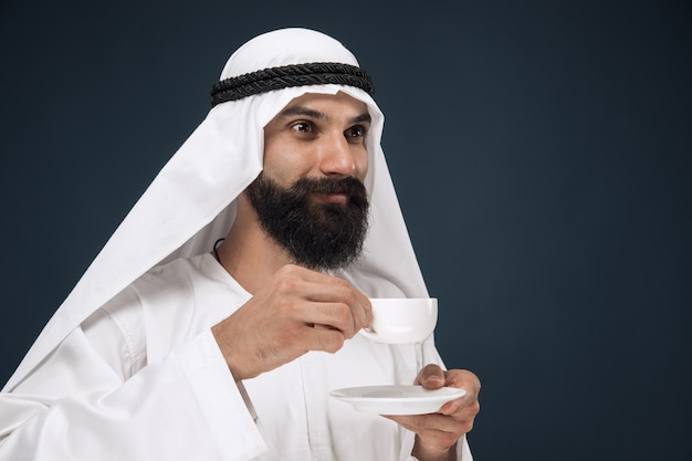 Portrait of arabian saudi man. young male model standing and drinking coffee or tea.
