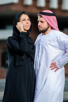 Portrait of arabic dressed yang couple play with mobile phone