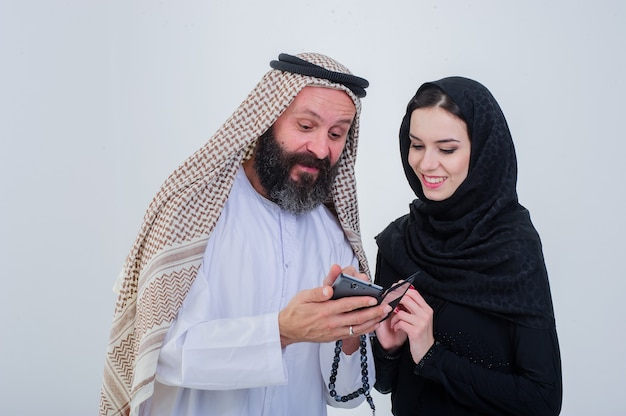 Portrait of arabic way dressed couple play with mobile phone.