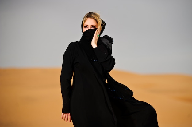 Portrait of arabic way dressed woman in yellow desert