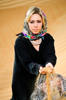 Portrait of arabic way dressed woman in yellow desert