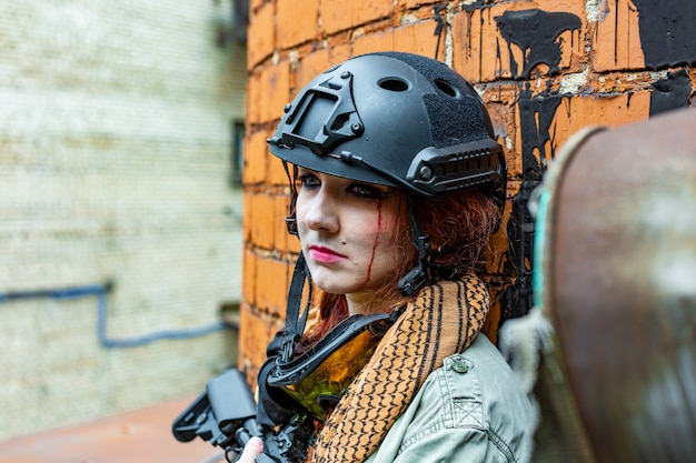 Portrait of army girl with rifle in camouflage clothes in urban scene, getting rest.