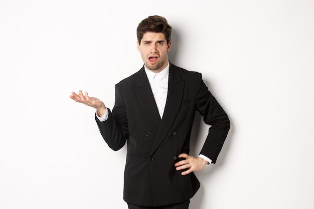 Ritratto di un uomo arrogante in abito nero, che sembra confuso e deluso, che si lamenta di qualcosa di strano, in piedi su uno sfondo bianco
