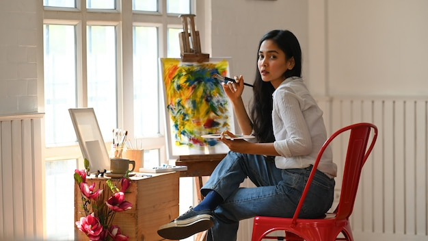 描画キャンバスの前に座っている肖像画のアーティストの女の子。