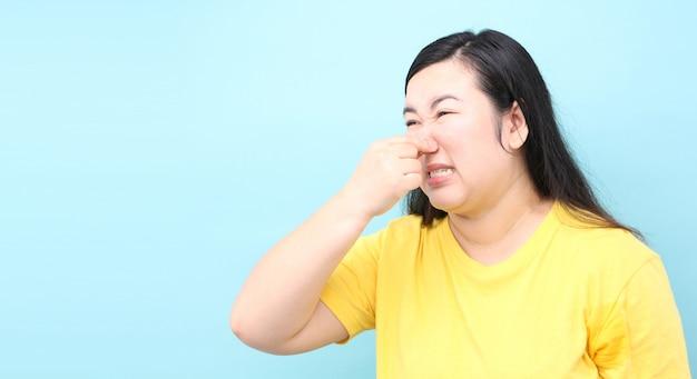Portrait asia woman feels foul, on blue background in studio