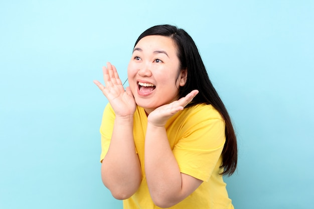 Portrait asia woman yelling and hand on his mouth, isolated on blue background in studio.