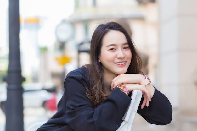 紺色の長袖シャツを着た肖像画のアジアの美しい女性は、都会の屋外公園の椅子に座って微笑んでいます。